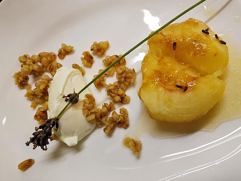 Gegrillte Pfirsichhälfte mit Ziegenkäsecreme.