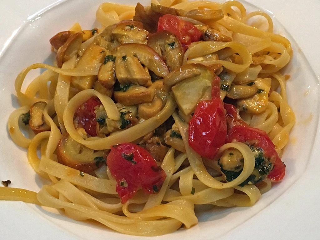 Tagliatelle mit Kaiserlingen und Tomaten.