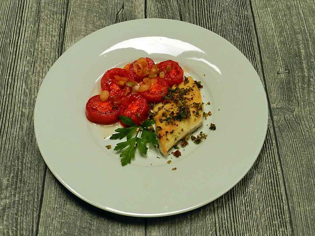Geschmorte Tomaten und gebratener Wolfsbarsch.